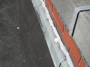 Counterflashing pulling from the wall, as well as old, flaking sealant.