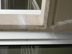 Efflorescence and cracking along underside of balcony.